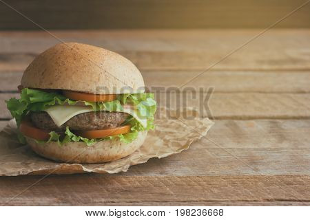 Homemade hamburger or sandwich on brown paper. Delicious sandwich hamburger with meat or pork ham cheese and fresh vegetable.