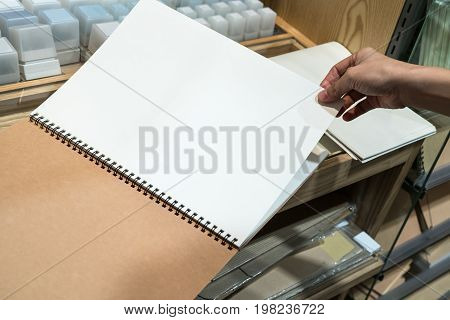 Hand turning a blank page of notebook at stationery shop for text and copy space.