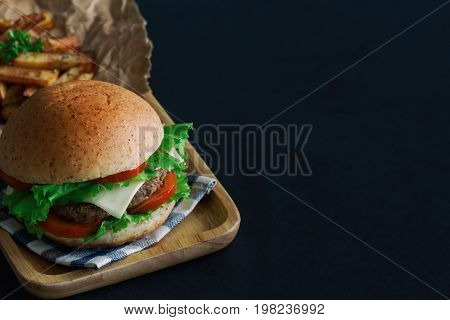 Homemade hamburger on plaid napkin with french fries. Delicious sandwich hamburger with meat or pork ham cheese and fresh vegetable.
