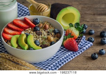 Muesli or granola on white bowl with fresh fruits nuts and cereal. Granola top with blueberries strawberries and avocado served with milk and honey for breakfast.Granola is healthy food for dieting. Start a day with granola or muesli.