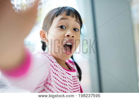 Little girl taking selfie with funny facial expression