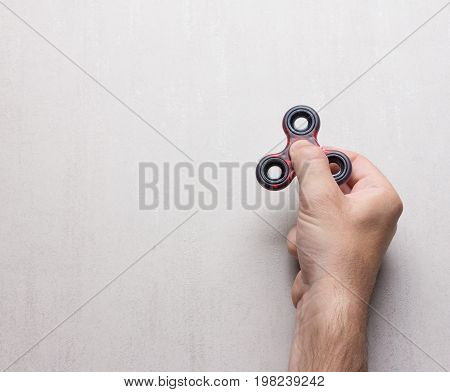 male hand with a popular toy spinner on a gray background with space for text