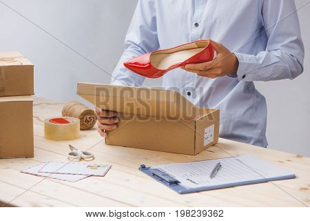 Close up deliveryman checking supplies and putting on cardboard box