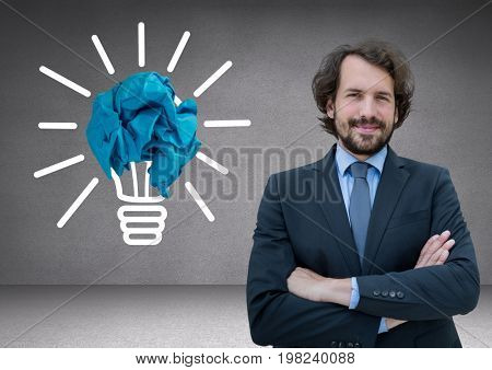 Digital composite of Man standing next to light bulb with crumpled paper ball