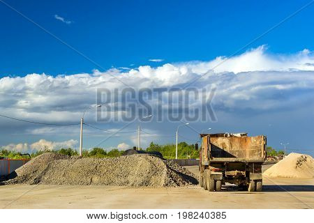 Heavy empty truck is waiting for loading of gravel. Construction of high-speed bypass road around Krasnoe Selo Saint Petersburg. Heavy machine equipment for civil industrial construction. Russia