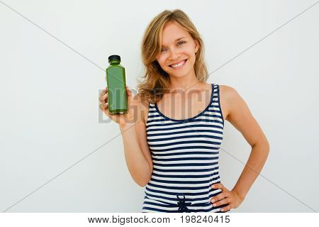 Cheerful beautiful young woman recommending good shampoo and looking at camera opposite white background. Portrait of happy woman holding hand on hip and showing new product. Choice concept