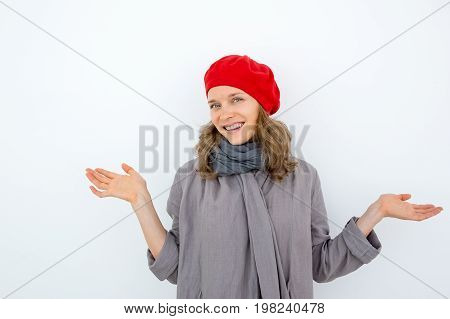Cheerful young French woman expressing uncertainty and looking at camera. Smiling funny girl in red beret and scarf shrugging shoulders. Misunderstanding concept