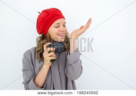 Enjoyable French woman smelling perfume and spraying it on wrist. Amazed young lady in red beret closing eyes while feeling scent. Style and personality concept