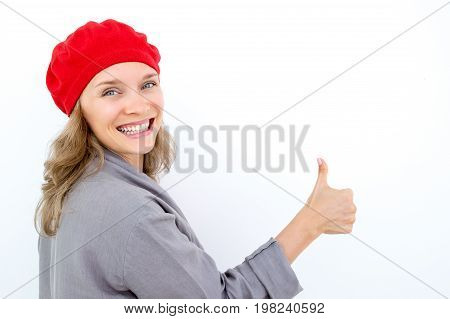 Excited young French woman showing thumb up and looking at camera. Cheerful girl in red beret turning around. She recommending product. Good choice concept
