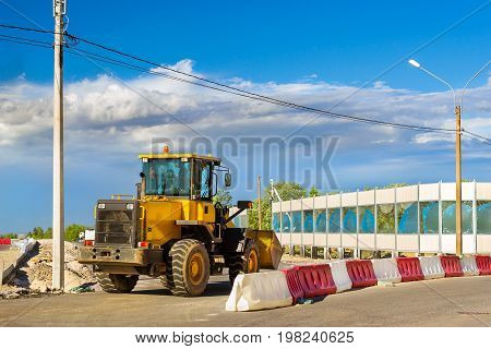 Bulldozer with bucket on construction of high-speed bypass road around Krasnoe Selo Saint Petersburg. Heavy machine equipment for excavation works at civil industrial construction. Russia