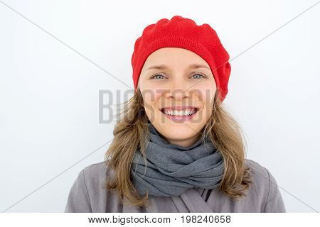 Portrait of happy carefree French lady in red beret. Cheerful beautiful young woman wearing scarf looking at camera. Optimist concept