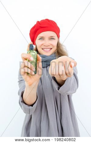 Happy stylish woman choosing perfume. Pleased young French woman wearing beret showing scent bottle and wrist. She offering to try new scent. Perfume company concept