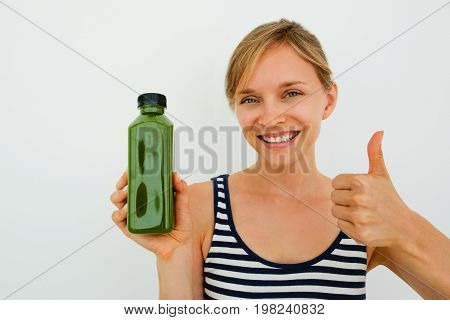 Happy young female blogger giving advice for shopping. Jolly beautiful woman holding bottle of smoothie and recommending it. She showing thumb up. Body care concept