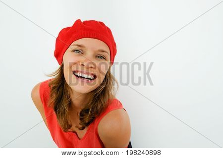 Playful elegant French woman smiling at camera. Romantic pretty girl posing for camera opposite white background. Portrait of happy young woman in beret bending. Flirting concept