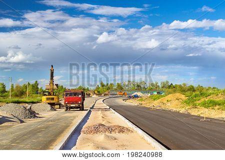 Crawler Excavator loads truck with rubble using bucket. Construction of high-speed bypass road around Krasnoe Selo Saint Petersburg. Heavy industrial machinery equipment for excavation works. Russia