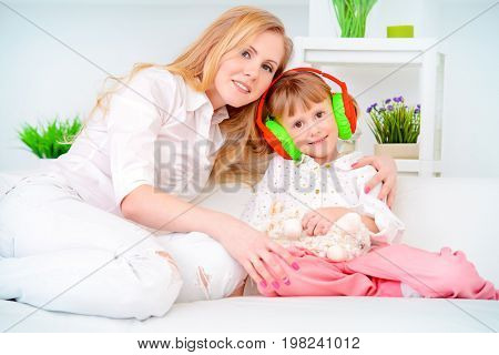 Little daughter laughing with her dear mother. Happy family spending time together.