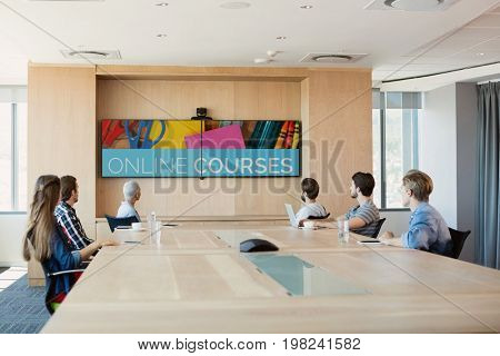 Digital composite of People looking at a TV with e-learning information in the screen