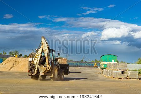Tractor with bucket performs excavation work. Construction of high-speed bypass road around Krasnoe Selo Saint Petersburg. Heavy machine equipment for excavation works industrial construction. Russia
