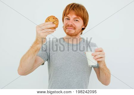 Closeup portrait of content adult red-haired man looking at camera, holding glass of milk and cookie. Isolated front view on grey background.