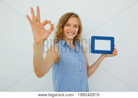 Closeup portrait of smiling young attractive woman looking at camera, holding empty picture frame and showing OK sign. Isolated view on grey background.