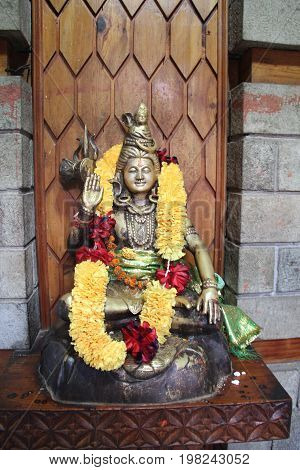 A statue of Shiva adorned with garlands of flowers
