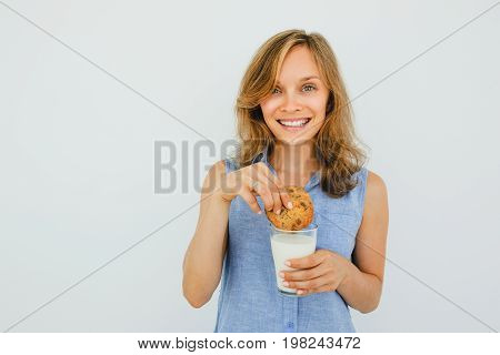 Closeup portrait of smiling young beautiful woman looking at camera, holding glass of milk and dunking cookie in it. Isolated front view on grey background.
