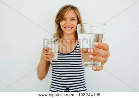 Closeup of smiling young attractive woman looking at camera, holding glass of milk and offering glass of water with focus on water. Isolated front view on grey background.
