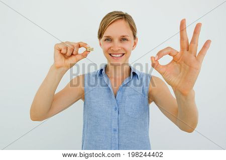 Closeup portrait of smiling young attractive woman holding coins stack, looking at camera and showing OK sign. Isolated front view on grey background.