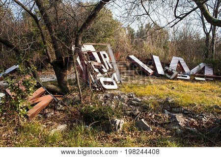 Old big letters of a sign store abandoned on grass