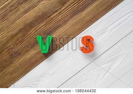 Letters VS on wooden background with copy space. The concept of making choice. Versus letters. Brown and white wooden background and colored letters VS.
