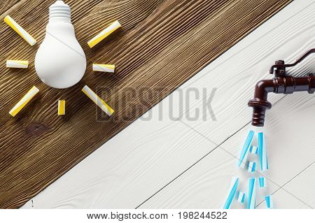 Brown tap and light bulb on wooden background. Two energy water and electricity. Eco concept. The tap with pouring water and idea bulb business concept.