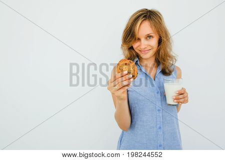 Closeup portrait of smiling young beautiful woman looking at camera, holding glass of milk and offering cookie. Isolated front view on grey background.