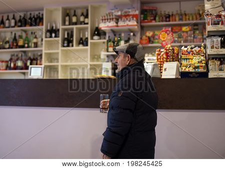 CHIOGGIA ITALY - DECEMBER 30: Elder man drinking beverage on December 30 2015
