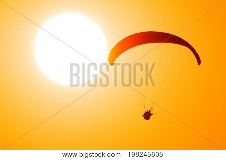 Paragliders in tandem fly against the sun and take selfie picture