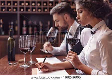 Sommeliers Tasting Wine In Cellar