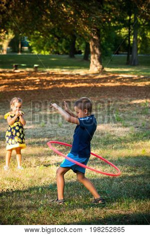 little boy play with hula hoop in park his sister watch him summer day