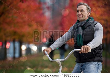 Digital composite of handsome man on a bike ride against leaves on field amidst trees