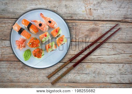 Salmon sushi served in plate against full frame of wooden wall