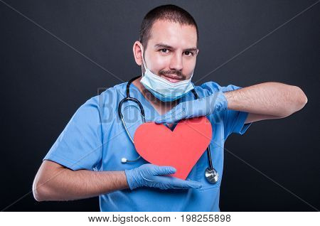 Cardiologist Wearing Scrubs Holding Red Heart Shape
