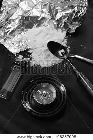 Black and white - Heroin, candle, syringe and tea spoon on black background.