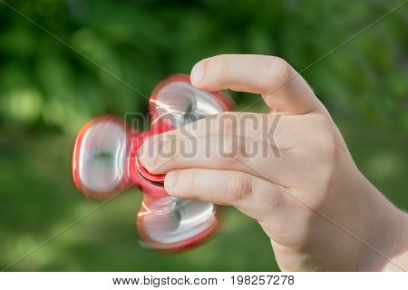 Fidget red spinner stress in hand.  Young boy play with red fidget spinner in outdoors, focus on spinner.
