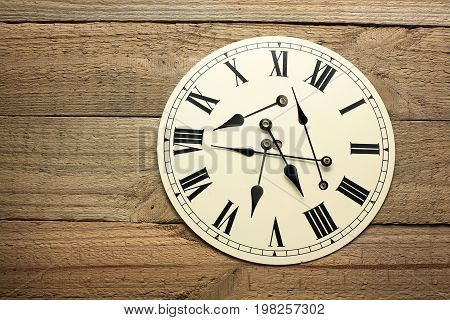Round Wall Clock on a Wooden Background
