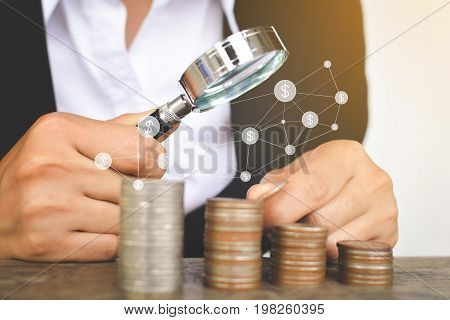 Business women using magnifying glass searching for money with icon