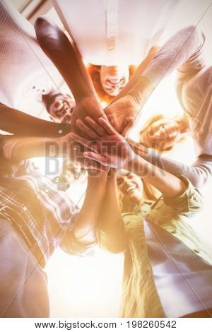 Directly below portrait of smiling business people stacking hands while standing in office