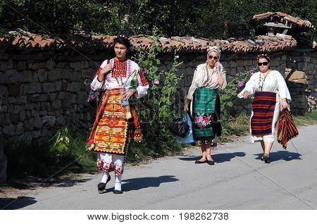 ARBANASI VILLAGE BULGARIA - JULY 22 2016: Bulgarian women wearing traditional Bulgarian costumes walk down the street