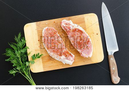 Pork loin on cutting board with knife on dark background. Overhead food shots. Cooking