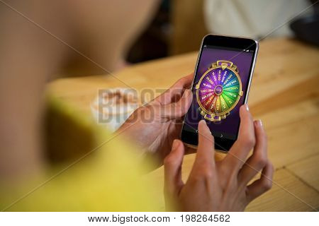 Multi colored fortune of wheel on mobile display against woman using mobile phone at table in cafe