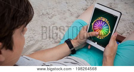 Wheel of fortune on mobile display against man using digital tablet on the beach