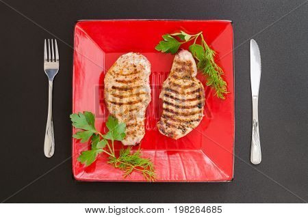 Roasted pork loin on red plate with fresh parsley and dill