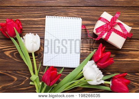 Box with present empty tag and bright red and white tulips flowers on wooden background. Selective focus. Place for text.
